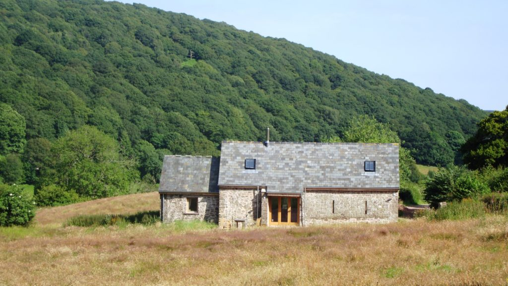 The Old Barn, one of our holiday cottages in the Brecon Beacons with Deri hill behind